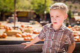 Little Boy Standing Against Old Wood Wagon at Pumpkin Patch