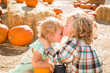 Sweet Little Boy Kisses His Baby Sister at Pumpkin Patch