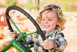 Adorable Young Boy Playing on an Old Tractor Outside