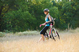 Young Attractive Woman Resting with Bike in the Beautiful Forest