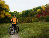 Cyclist with Bike in the Beautiful Autumn Forest