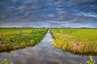 canal in Dutch farmland with reflected sky