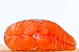 Red is a piece of salmon on a white background