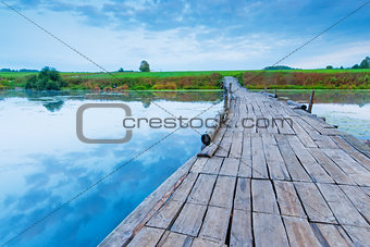 wooden bridge over a small lake in the early morning