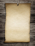 old wanted paper or parchment pinned by nail to grunge wooden ba