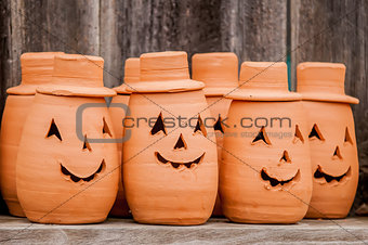 clay pumpkins standing happy near the wood fence