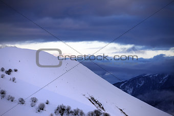 Off-piste slope and cloudy sky at sunset