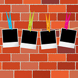 Blank photo frames with clothes pegs on rope over brick wall