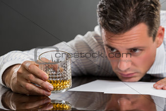 Sad businessman drinking alcohol