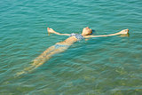 Teen girl lying on the sea water surface