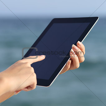 Close up of a woman hands holding and browsing a digital tablet on the beach