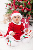 Pretty baby girl in santa costume sitting