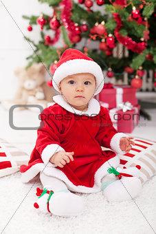 Pretty baby girl in santa costume sitting