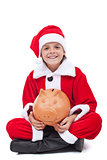 Happy boy in santa costume with piggy bank