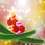 Two burning candles with bows on Christmas tree branch