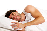 Man laid in white bed smiling
