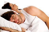 Man laid in white bed next to a woman sleeping