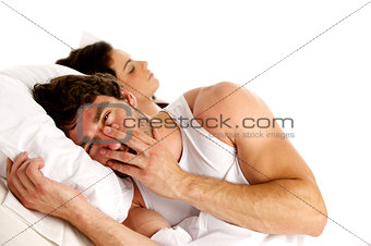 Tired man laid in white bed next to a sleeping woman