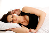 Woman laid in white bed next to a sleeping man