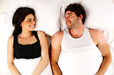 Man and woman laid in bed smiling to each other