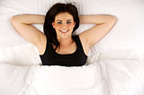 Woman laid in bed relaxed looking up at the camera smiling