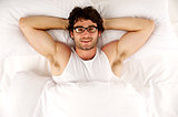 Man laid in white bed looking up at the camera smiling