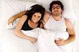 Man and woman laid in white bed looking up at the camera smiling