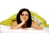 Beautiful woman in bed under a green duvet