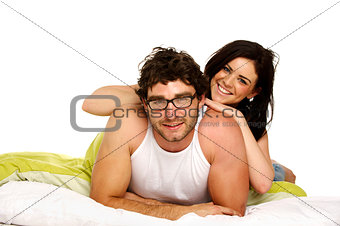 Beautiful couple in bed smiling at the camera