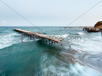 Evening sea surf, ruined pier and Moon in sky (Black Sea, Bulgar