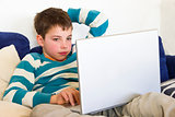 Thoughtful kid work on a computer through the wireless network