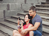 Young couple of tourists sitting on steps