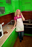 Housewife, speaks on a phone in the kitchen
