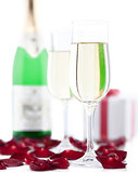 Two glasses of champagne, gift box, rose petals on white backgro