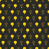 Seamless vector pattern or texture with yellow light bulbs on black background