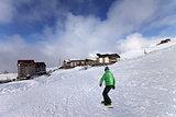 Hotels on ski resort and snowboarder on slope
