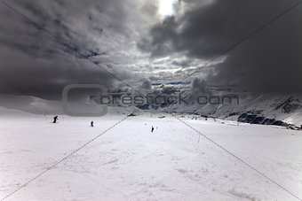 Ski slope, skiers and sky with storm clouds