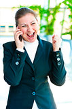 Young brunette enjoys success with the phone on office background