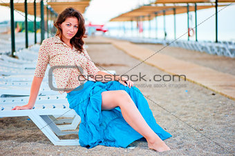 Beautiful young girl posing on a beach lounger