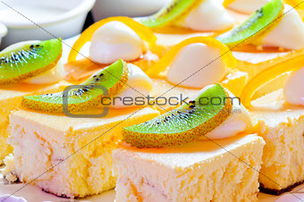 Cottage cheese pie decorated with a slice of kiwi and orange zest