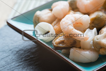 Fresh raw seafood mix of prawns mussels and squid on serving pla
