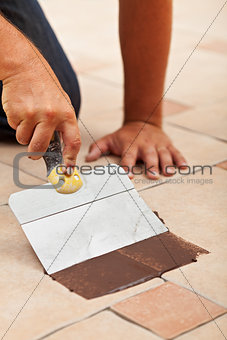 Applying the joint material on ceramic floor tiles