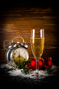 Christmas balls and vintage clock with glass of champagne