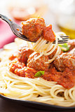 spaghetti with meatballs in tomato sauce on fork