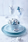 Silver and blue christmas ornaments in a cup