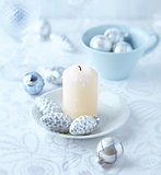Candle and glass ornaments on a christmas table