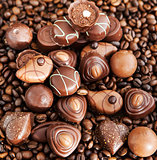 Assorted chocolate pralines on coffee beans background
