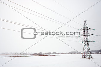 power line in the middle of the field in winter