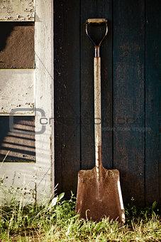 Old Vintage Metal Shovel with rust on blue barn Door.