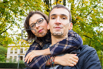 Portrait of love couple embracing outdoor looking happy